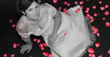 Eine junge Frau die auf einem schwarzen Fussboden mit roten Rosenblüten sitzt, sie hat ein weisses Hochzeitskleid an, die Haare hochgesteckt und bunte Sterne auf ihrer rechten Schulter tätowiert