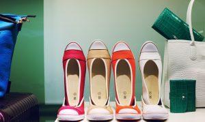 vier paar Ballerina Schuhe jeweils in rot, beige, orange und weiss, der zweite Schuleh ist in den ersten so reingestellt das er steht, links eine blaue Tasche und rechts eine weisse Tasche mit grünem Geldbeutel