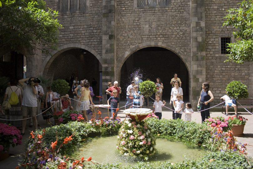 mehrere Leue stehen um einen kleinen Springbrunnen der mit Blumen geschmückt ist und auf dessen Wasserstrahl ein weisses Ei tanzt