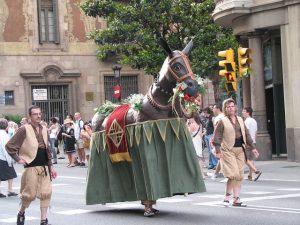 eine Person die ein sehr realistisches Pferdekostüm trägt und durch die Strafen läuft, links und recht begleiten es zwei als Bauern verkleidete Männer