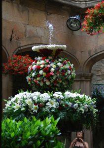 ein Springbrunnen im Vorhof einer Kirche der mit Blumen geschmückt ist und auf dem Wasserstrahl tanzt ein Ei