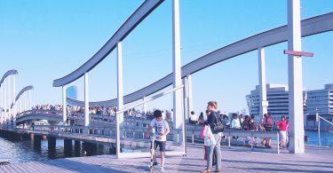 Menschen die auf dem Steg vom Hafen Barcelonas spazieren gehen