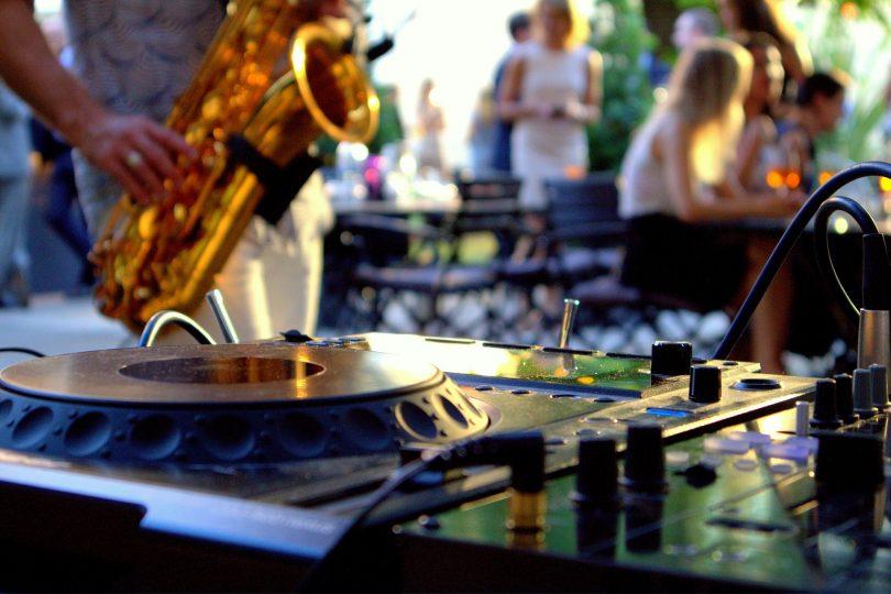 Nahaufnahme eines Mischpults und im Hintergrund ein Saxofonspieler, Tische, Stühle und laufende Leute
