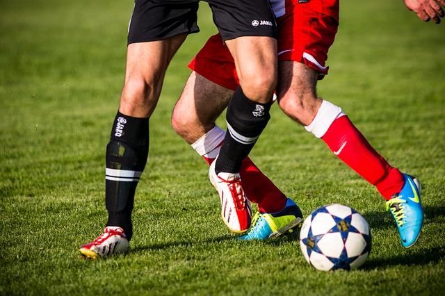 zwei Fußballspieler, einer in schwarz der andere in rot die im stadium auf grünem gras um den Fußball kämpfen