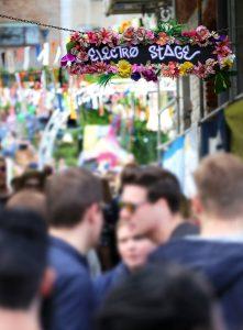 eine mit Blumen geschmückte Straße mit vielen Menschen und recht oben ein schwarzes Schild mit Blumen außen herum und mit weißer Schrift steht electro stage geschrieben