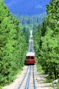 ein gang durch den dichten Wald wo die rote Bahn auf schienen auf den Berg fährt