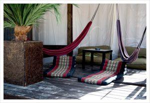 chill out Zone einer Strandbar mit einer roten und einer lilanen Hängematte und zwei Sitzkissen darunter