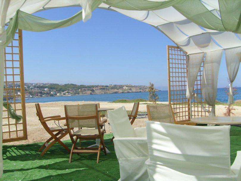 weisser Klappstühle einer Strandbar mit weissen und hellgrünen Tüchern als Sonnenschutz darüber