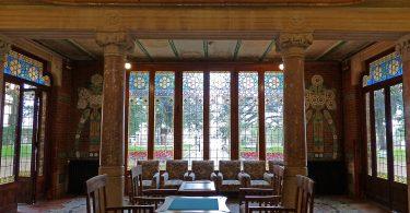ein großer Saal mit großen Glasfenstern an allen Wänden, eine hohe gewölbte Decke und in der Mitte ein Holztisch mit vier Holztischen drum herum