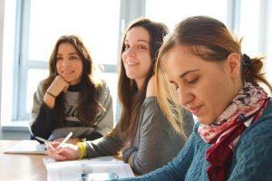 drei junge Frauen die an einem Tisch sitzen zwei lächeln nach vorne und eine schaut in ein Buch