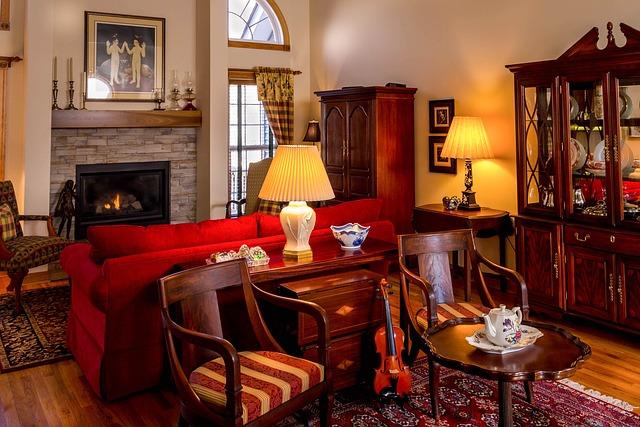 ein Wohnzimmer mit einem Kamin, davor steht ein rotes Sofa und hinter dem Sofa eine Kommode mit einer lampe, zwei Holzstühle an den Seiten und ein kleiner runder Holztisch davor