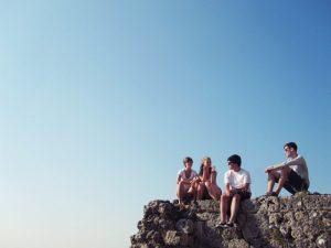 vier Jugendliche die auf einem Felsvorsprung sitzen danieder klarer blauer Himmel