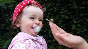 ein kleines Mädchen mit Schnuller im Mund, rosaner Jacke und roter Mütze die bei dem Anblick einer kleinen Schnecke übers ganze Gesicht lächelt