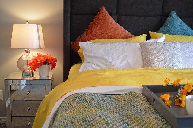 die rechte Seite eines Doppelbetts mit gelber Bettwäsche und orangenen Kissen, auf dem Nachtkästchen steht eine weiße Stehlampe und orangen Blumen