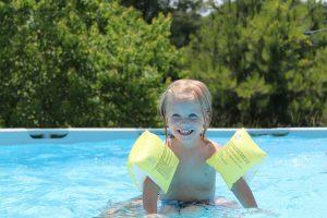 Kleines Kind lächelt fröhlich während es im Pool spielt