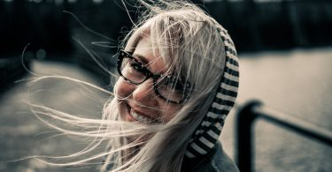 Eine junge Frau auf einer Brücke mit einer schwarz-weiss gestreiften Kapuze, langen blonden Harren und einer schwarzen Brille die in die Kamera lächelt
