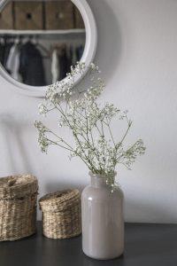 Schlafzimmerkomode mit grauer Vase und weissen Blümchen, oberhalb ein runder Spiegel in dem der Kleiderschrank zu sehen ist