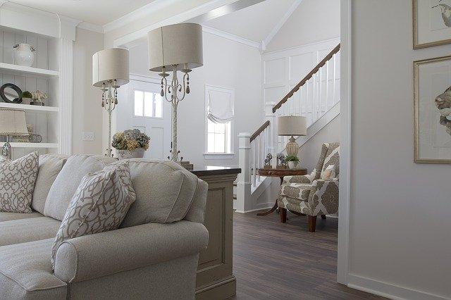 Minimalistisches, weisses Wohnzimmer mit Sofa, zwei Tischlampen, ein Regal und auch die weisse Eingangstür und die Treppen sind zu sehen