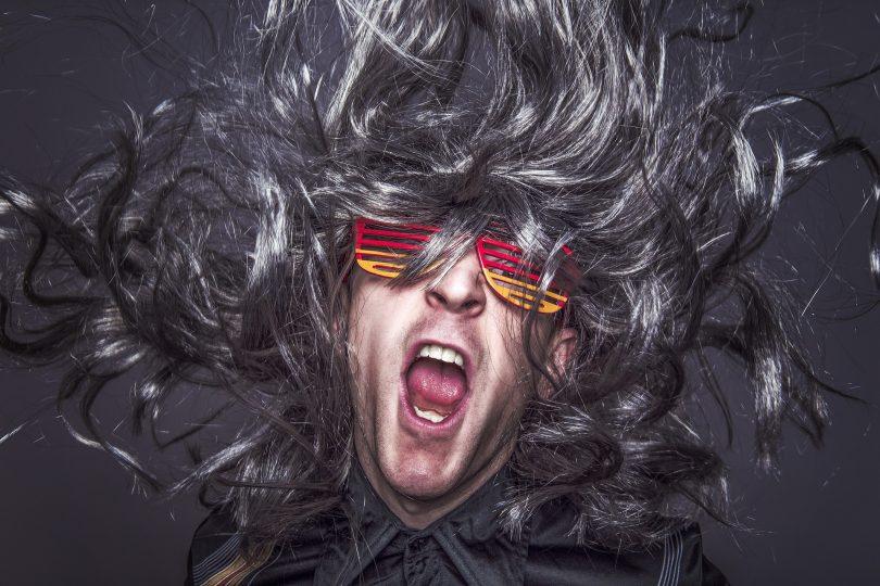ein Mann mit dunkelgrauen Haaren, einer rot gelben Faschingsbrille und einem grauem Hemd der mit offenem Mund schreit