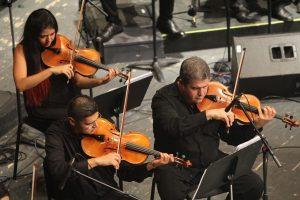 zwei Männer und eine Frau die ganz in schwarz gekleidet Geige spielen
