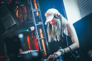 eine DJ mit blonden langen Haaren, einem Cappy und Kopfhörern die auf einer Bühne Musik auflegt