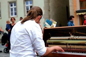ein Mann der etwas auf einem Klavier mitten auf der Straße spielt, er hat lange braune Haare zu einem Pferdeschwanz zusammen gebunden und ein weisses Hemd an, man sieht ihn von Hinten und Leute um ihn herum