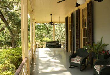 Terrasse eines Ferienhauses mit Sonnenschein und Bäumen im Hintergrund