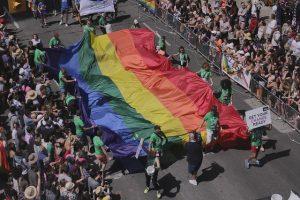 mehrere Personen mit grünen T-Shirts die eine riesen Flagge mit Regenbogenfarben auf einer Straße vorwärts bringen, links und rechts stehen viele Menschen