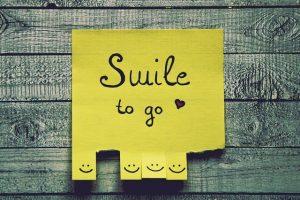ein gelbes Postit das auf einer Holzwand geklebt ist und auf dem steht Smile to go und unten sind lachende Gesichter zum abreissen