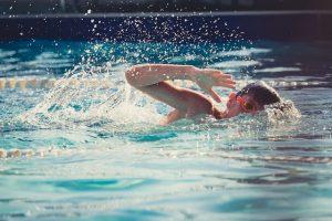Jugendlicher mit Taucherbrille beim Kraulschwimmen