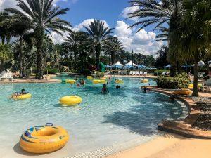 Pool mit gelben Luftringen Liegestühle und Palmen am Beckenrand