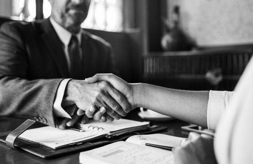 schwarz weiss Foto von zwei Personen die sich über einen Tisch die Hände schütteln