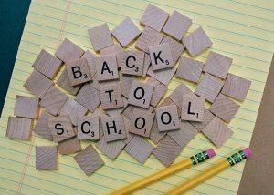 Scrabble Spielsteine auf gelb liniertem Papier zum Satz back to school aufgereiht und zwei gelbe Bleistifte daneben