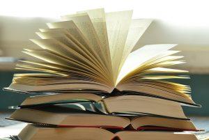 gestappelte offene Bücher wobei das oberste einen Fecher mit den Seiten bildet