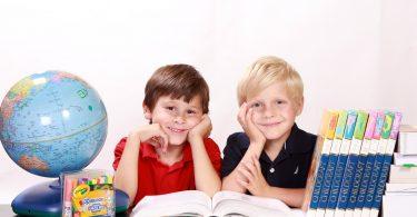 ein brünetter und ein blonder Junge an einem dunkelbraunem Holztisch umgeben von einem Globus, Büchern und Farbstiften