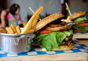 üppiger Hamburger mit Pommes Frites in Metaltöpfchen auf Holzbrett mit blau weiss karierter Serviette