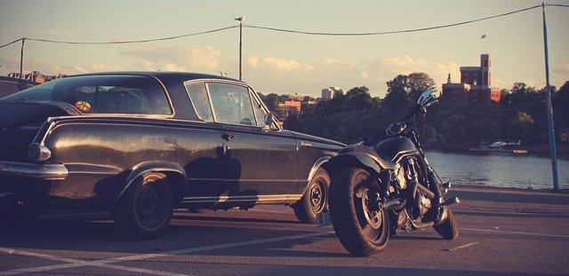 Parkplatz an einer Meeresbucht auf dem ein schwarzes Auto und ein schwarzes Motorrad stehen