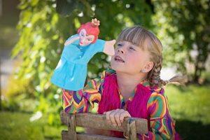 Ein blondes Mädchen mit zwei Zöpfen das auf einem Holzstuhl sitz, ein farbenfrohes Kostüm an hat und mit einer Marionette spielt