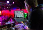 Dj in einer Disco der Musik mit Hilfe eines Laptops auflegt
