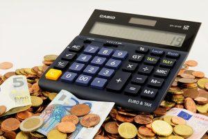schwarzer Taschenrechner auf einem Haufen von Münzen und Geldscheinen