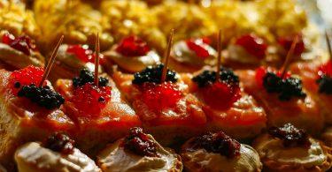 Nahaufnahme verschiedener Tapas und Pintxos mit Gänseleber, Lachs und Kartoffelomlett