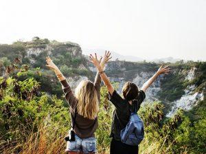 Zwei Frauen mitten in der Natur die vor Freude die Arme in die Luft reisen
