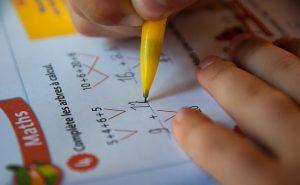 zwei Kinderhände mit einem gelben Bleistift bei der Lösung verschiedener Summen