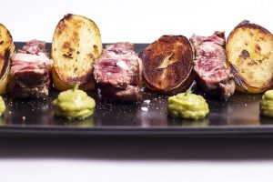 schwarzer rechteckiger Teller mit Fleisch Medium, Bratkartoffeln und Guacamole