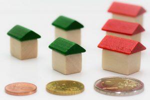 kleine Holzhäuser, drei mit grünem Dach und drei mit rotem Dach und davor ein einer Reihe Euromünzen