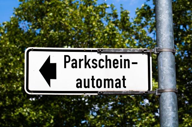 weisses Schild mit schwarzem Pfeil und geschrieben Parkscheinautomat, im Hintergrund Blätter eines Baumes