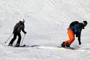 Ein Skifahrer und ein Snowboardfahrer auf der Schneepiste