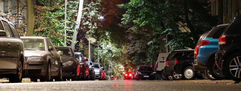 Eine breite Allee mit geparkten Autos auf beiden Seiten
