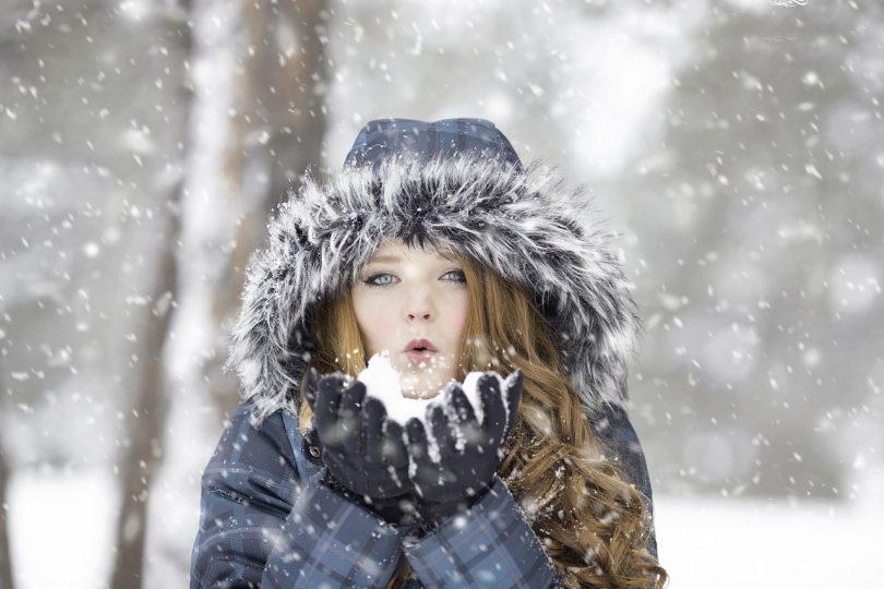 Frau mit langen lockigen Haaren, blauem Anorak und Handschuhen bläst aus ihrer Hand Schnee entgegen