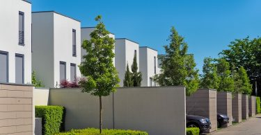 Weisse Einfamilienhäuser mit individuellen Parkplätzen